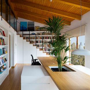 Modern inredning av ett arbetsrum, med ett bibliotek, vita väggar, ljust trägolv, ett inbyggt skrivbord och beiget golv