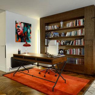 Idéer för ett mellanstort modernt hemmabibliotek, med röda väggar, mörkt trägolv, ett fristående skrivbord och brunt golv