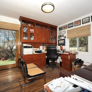 Cette photo montre un grand bureau tendance de type studio avec un mur blanc, un sol en contreplaqué, aucune cheminée, un bureau intégré et un sol marron.