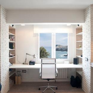 Foto på ett mellanstort maritimt hemmastudio, med vita väggar, laminatgolv, ett inbyggt skrivbord och beiget golv