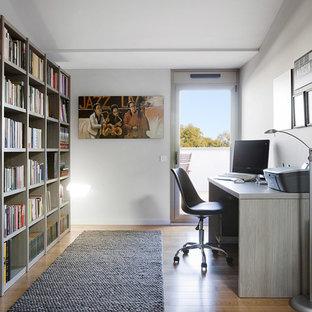 Imagen de despacho contemporáneo, de tamaño medio, sin chimenea, con paredes blancas, suelo de madera en tonos medios, escritorio independiente y suelo marrón