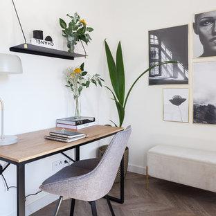 Стильный дизайн: домашняя мастерская среднего размера в скандинавском стиле с белыми стенами, полом из ламината, отдельно стоящим рабочим столом и коричневым полом - последний тренд