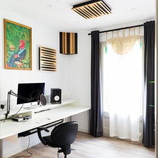 Diseño de despacho contemporáneo con paredes blancas, suelo de madera clara, escritorio independiente y suelo beige