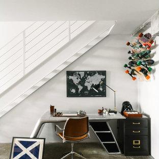 Ejemplo de despacho industrial, pequeño, sin chimenea, con paredes blancas, suelo de cemento y escritorio empotrado