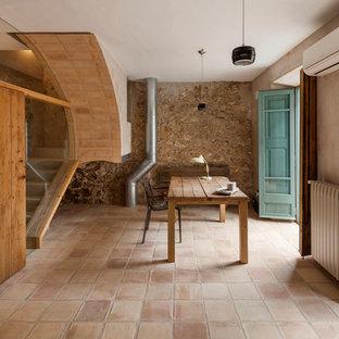 Medelhavsstil inredning av ett stort hemmabibliotek, med bruna väggar, klinkergolv i terrakotta och ett fristående skrivbord