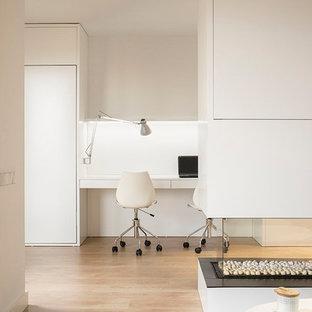 Ejemplo de despacho nórdico, pequeño, con paredes blancas, suelo de madera en tonos medios, chimenea de doble cara, escritorio empotrado y suelo marrón