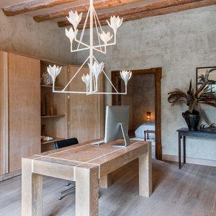 Foto de despacho mediterráneo con paredes grises, suelo de madera clara y escritorio independiente