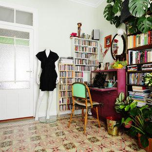 Modelo de despacho ecléctico, sin chimenea, con paredes verdes, escritorio independiente y suelo multicolor