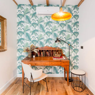 Bild på ett litet tropiskt hemmabibliotek, med flerfärgade väggar, mellanmörkt trägolv, brunt golv och ett fristående skrivbord