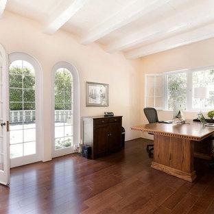 ロサンゼルスの中サイズのトラディショナルスタイルのおしゃれな書斎 (ピンクの壁、ラミネートの床、暖炉なし、自立型机、茶色い床) の写真