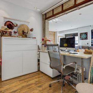 Imagen de despacho ecléctico con paredes blancas, suelo de madera en tonos medios, escritorio independiente y suelo marrón