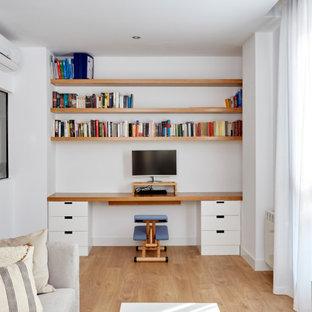 Foto på ett mellanstort funkis hemmastudio, med vita väggar, ljust trägolv och ett inbyggt skrivbord