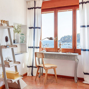 This is an example of a small nautical study in Other with white walls, terracotta flooring, no fireplace, a freestanding desk and red floors.