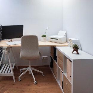 Идея дизайна: маленькая домашняя мастерская в скандинавском стиле с белыми стенами, полом из ламината, отдельно стоящим рабочим столом и бежевым полом