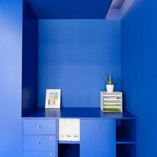 Foto di un piccolo studio moderno con libreria, pareti blu, pavimento in cemento, scrivania incassata e pavimento blu
