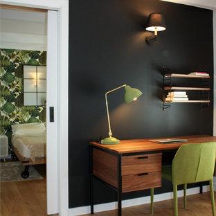 Diseño de despacho actual, pequeño, sin chimenea, con paredes negras, suelo de madera en tonos medios, escritorio independiente y suelo marrón