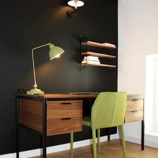 Immagine di un piccolo ufficio moderno con pareti nere, pavimento in legno massello medio, scrivania autoportante e pavimento marrone