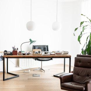 Imagen de despacho contemporáneo con paredes blancas, suelo de madera clara, escritorio independiente y suelo beige