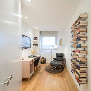 Modelo de despacho contemporáneo, de tamaño medio, sin chimenea, con paredes blancas, suelo de madera en tonos medios y escritorio empotrado