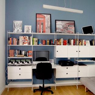 マドリードの小さいコンテンポラリースタイルのおしゃれなアトリエ・スタジオ (青い壁、暖炉なし、造り付け机、ラミネートの床、茶色い床) の写真