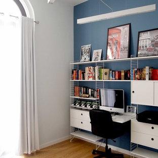 Ispirazione per un piccolo atelier design con pareti blu, nessun camino, scrivania incassata, pavimento in laminato e pavimento marrone