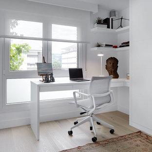 Imagen de despacho actual, de tamaño medio, sin chimenea, con paredes blancas, suelo de madera en tonos medios y escritorio empotrado