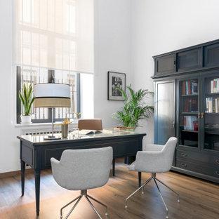 Ejemplo de despacho tradicional renovado, grande, con paredes blancas, suelo de madera en tonos medios, escritorio independiente y suelo marrón