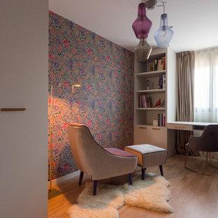 Modelo de despacho contemporáneo, de tamaño medio, con paredes multicolor, suelo de madera en tonos medios, escritorio empotrado y suelo marrón