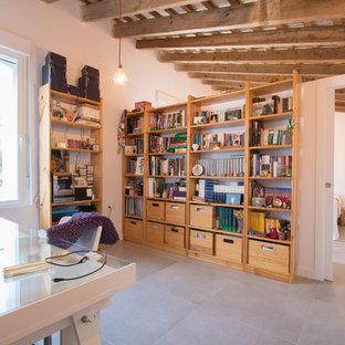 Foto de sala de manualidades actual con paredes blancas, escritorio independiente y suelo gris
