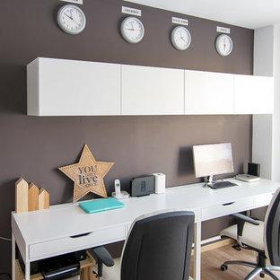 バレンシアの中くらいの北欧スタイルのおしゃれな書斎 (黒い壁、ラミネートの床、自立型机) の写真