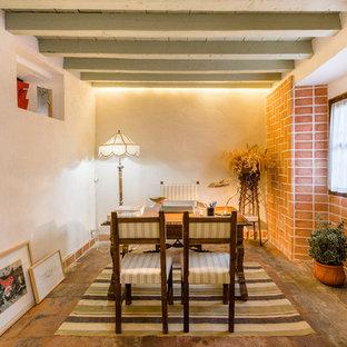Diseño de despacho mediterráneo con paredes blancas, escritorio independiente, suelo naranja y suelo de baldosas de terracota