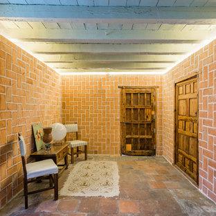 Ejemplo de despacho clásico renovado con parades naranjas, suelo de baldosas de terracota y suelo marrón