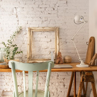This is an example of a small traditional study room in Other with white walls, concrete floors and a freestanding desk.