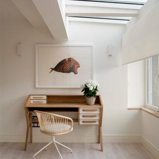 Пример оригинального дизайна: домашняя мастерская среднего размера в скандинавском стиле с белыми стенами, полом из ламината, отдельно стоящим рабочим столом и коричневым полом без камина