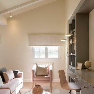 Diseño de despacho clásico renovado, de tamaño medio, con paredes beige, escritorio empotrado, suelo laminado y suelo marrón