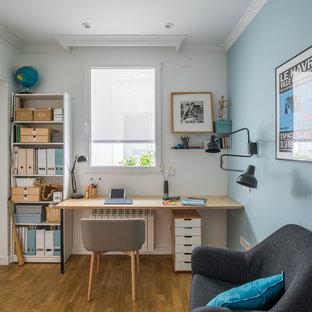 Ejemplo de despacho actual con paredes azules, suelo de madera en tonos medios, escritorio empotrado y suelo marrón