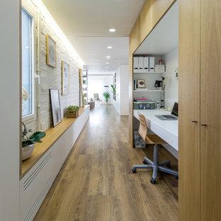 Modelo de despacho contemporáneo, sin chimenea, con paredes blancas, escritorio empotrado y suelo de madera clara