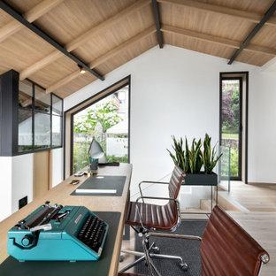Modelo de despacho madera, tropical, grande, con paredes blancas, suelo de madera clara, escritorio independiente y suelo beige