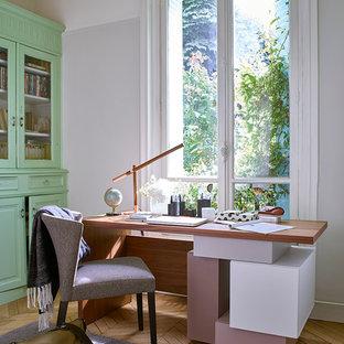 Diseño de estudio clásico renovado, de tamaño medio, con paredes blancas, suelo de madera en tonos medios y escritorio independiente
