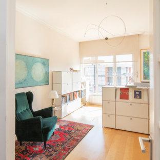 Ejemplo de despacho actual, grande, con paredes blancas, suelo de madera clara, escritorio independiente y suelo beige