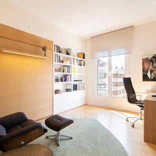 Modelo de despacho actual, de tamaño medio, con paredes blancas, suelo de madera clara y escritorio independiente