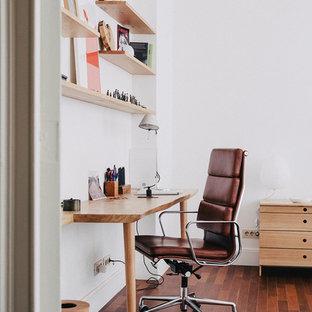Modelo de despacho retro, pequeño, sin chimenea, con paredes blancas, suelo de madera oscura, escritorio empotrado y suelo marrón