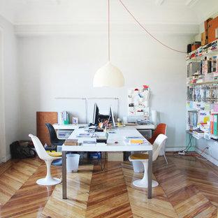 Bild på ett mellanstort funkis hemmabibliotek, med vita väggar, ljust trägolv och ett fristående skrivbord