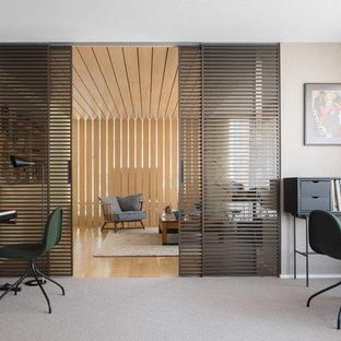 Imagen de estudio actual, grande, sin chimenea, con moqueta, suelo gris, paredes beige y escritorio independiente