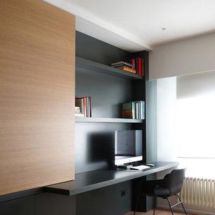 Diseño de despacho contemporáneo, de tamaño medio, con suelo de madera en tonos medios, paredes negras y escritorio empotrado