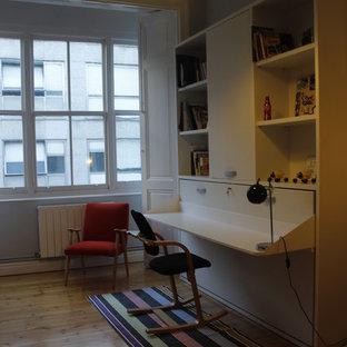 Ispirazione per un piccolo atelier classico con pareti bianche, parquet chiaro, camino classico, cornice del camino in pietra e scrivania incassata