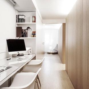 Modelo de despacho escandinavo, pequeño, sin chimenea, con paredes blancas, suelo de madera clara y escritorio empotrado