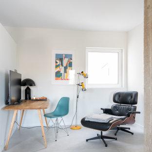 Diseño de estudio actual con paredes blancas, suelo de cemento, escritorio independiente y suelo gris