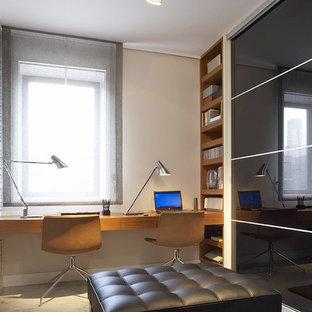Imagen de estudio contemporáneo, de tamaño medio, sin chimenea, con paredes blancas, suelo de cemento, escritorio empotrado y suelo gris