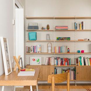 Diseño de estudio contemporáneo, grande, sin chimenea, con suelo de madera en tonos medios, suelo marrón, paredes blancas y escritorio independiente